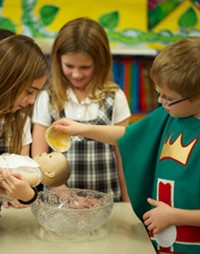 Students performing a baptism on doll